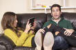 Couple on sofa relaxing and using tablet and smart phone