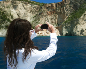 young woman photographs the island in Greece