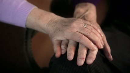 Woman caressing old mans hand