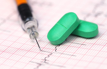 Electrocardiograph with pills and syringe