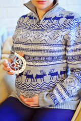Pregnant woman belly in cozy sweater