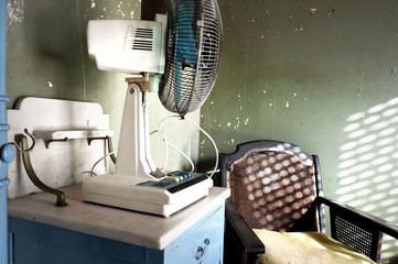 Electric fan and armchair in an old bedroom