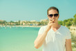 Leinwandbild Motiv Man in sunglasses smoking cigar on vacation.