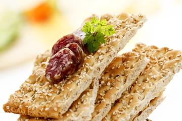 Knäckebrot mit Sesamkörnern, gestapelt, Salamischeiben