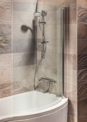 detail of a modern bathroom with bath and shower
