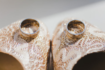 wedding rings close up on bride's shoes
