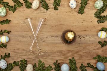 Osterdekoration, Sektflasche und Sektgläser auf Holz