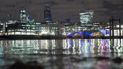 City of London nighttime lights reflected in the Thames.