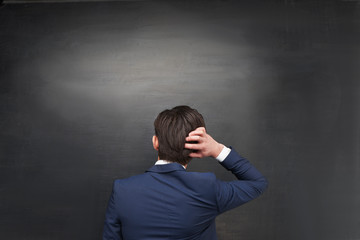Back photo of pensive businessman on chalkboard background
