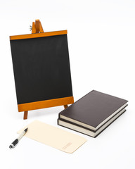 Blank black board with wooden stand and books.