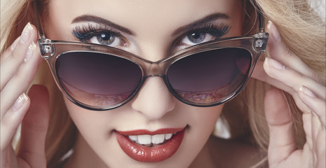 Seductive happy woman looking over sunglasses