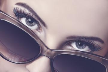 Seductive woman closeup portrait looking over sunglasses