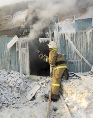 Firefighter extinguishes a fire in a wooden house