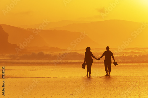 Staande foto Strand couple walking on beach at sunset