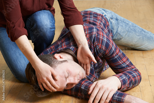 Woman Placing Man In Recovery Position After Accident - 78381635