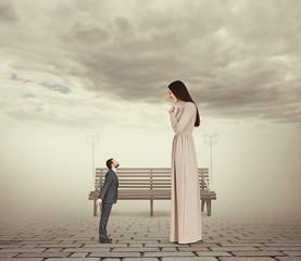 woman looking at small kissing man