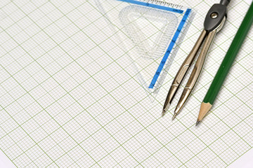 Mathematical instruments and pencil on graph paper.