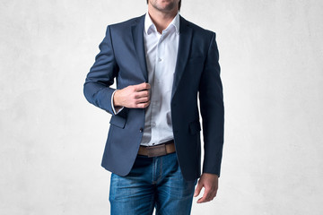 Man in trendy suit  standing alone holding his jacket with