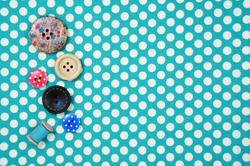 Buttons on blue polka dot fabric background