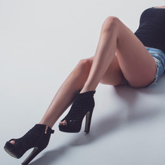 Perfect female long legs wearing black high heels ankle boots