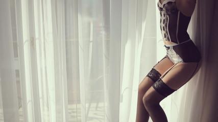 Beautiful model in lingerie against the window hotel