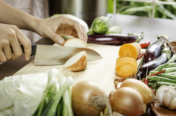 image of a woman cutting onion with vegetables around her