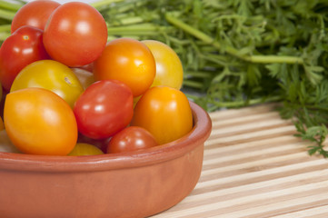 Tomates Cherry en cazuela de barro sobre tabla de Bambú