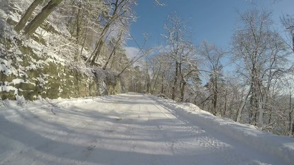 Car speeding on a beautiful forest road in winter