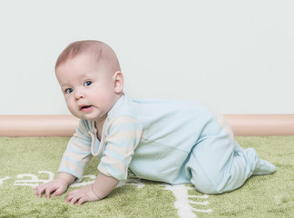 The child creeps on a soft green carpet isolated