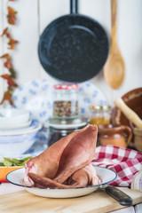 Orejas de cerdo crudas en la mesa de la cocina