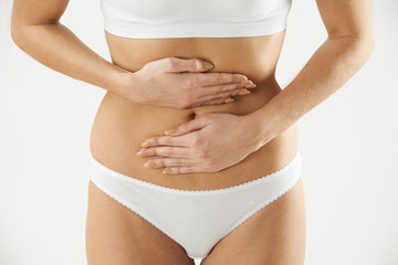 Close Up Of Woman In Underwear Holding Stomach In Pain