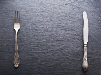 Silver cutlery on a dark grey background.