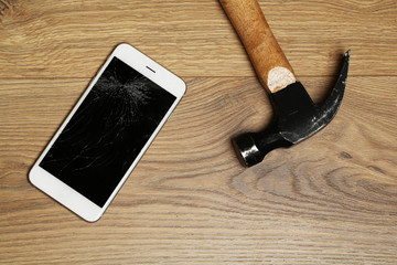 Broken iPhone with hammer on wooden background