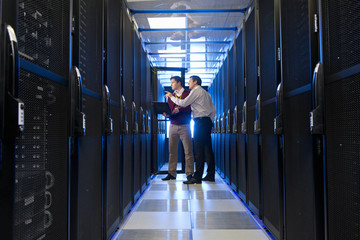 Manager and technician, with laptop, talking in aisle of server room