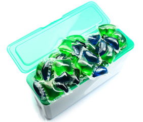 Gel capsules with laundry detergent in box isolated on white