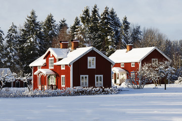 old red farm set in a wintery rural landscape, sweden