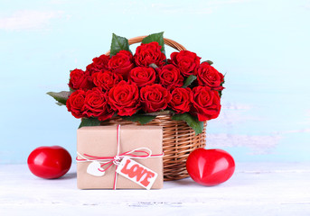 Bouquet of red roses in basket with present box