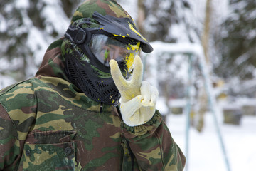 Closeup of paintball player in mask with paint splash showing pe