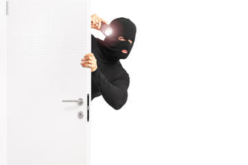 Burglar with flashlight entering through a door