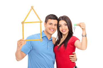 Couple holding tape measure in form of house and key