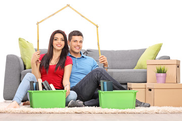Young couple sitting by a bunch of moving boxes