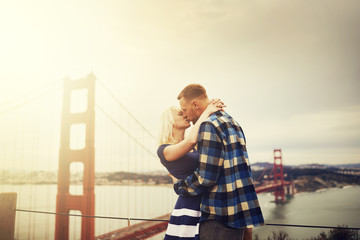 romantic couple kissing at golden gate bridge with lens flare