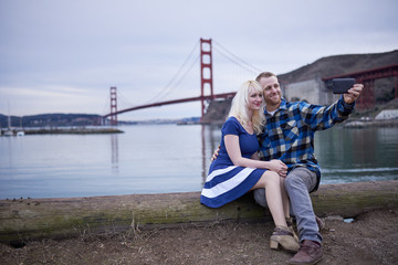 romantic couple taking selfie with golden gate bridge