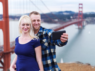 couple taking selfie in front of golden gate bridge