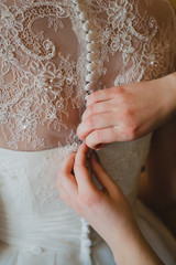 bridesmaid's hands buttoning wedding dress
