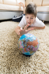 Boy studying globe in the room
