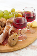 wine with dry fruits, cookies and cheese