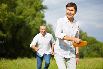Frau und Mann spielen mit Frisbee im Sommer