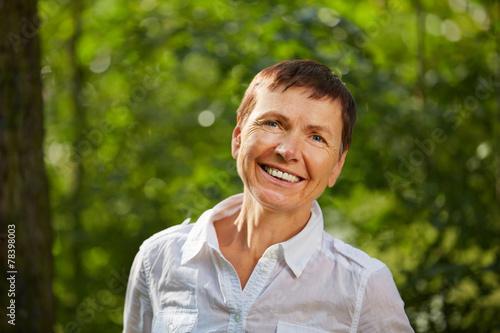 canvas print picture Lachende alte Frau draußen im Wald
