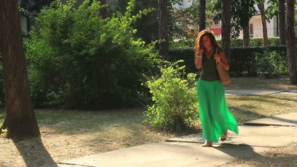 Attractive brunette walk in the park and talk on the mobile